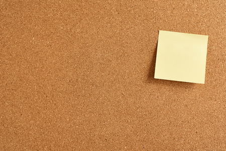 Cork board with yellow paper blank note, close up Standard-Bild