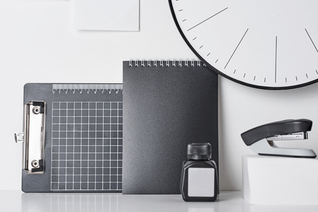 Office supplies, sticky blanks and round clock on white wall, front view. Office workplace desk