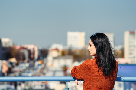Young woman on roof of building looks at urban landscape. Fashion outdoor portrait