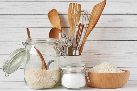 Kitchen tools and glass jar with rice on white table, front view. Kitchen utensils background