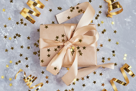 Gift box wrapped in kraft paper with golden bow and confetti in shape star, close up Stock Photo