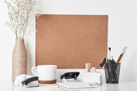 Cork board with office supplies, cup and plant in bottle vase on white background. Home office workplace