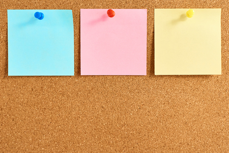 Tableau de liège avec des notes vierges colorées épinglées