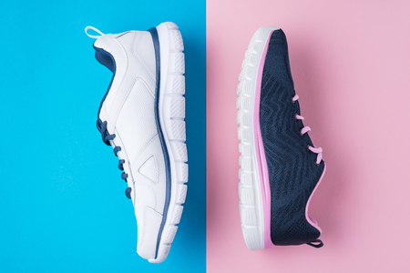 Male and female sport shoes on pink and blue background, flat lay top view. Running sneakers on colorful background