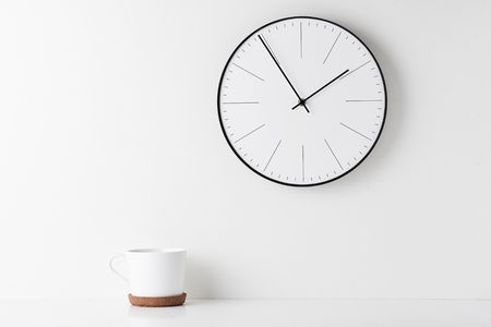 Front view desk with round wall clock and cup on white background. Home office minimal workspace desk Imagens
