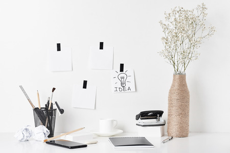 Office supplies, sticky notes and plant in bottle vase on white background, front view. Home office workplace Imagens