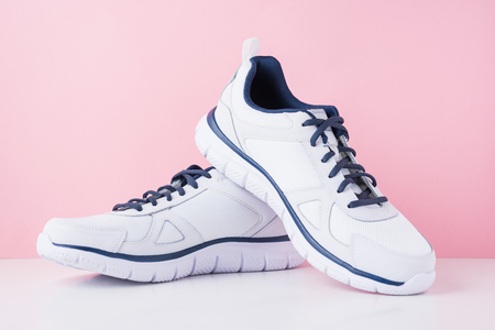 Male sneakers for run on pink background. White fashion stylish sport shoes, close up