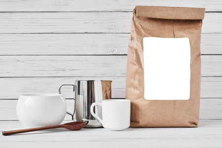 Coffee cup, craft paper bag and stainless pitcher on white background, copy space