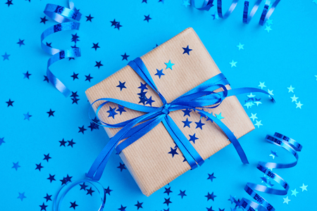 Gift box wrapped in kraft paper with bow and confetti in shape star on blue background, close up