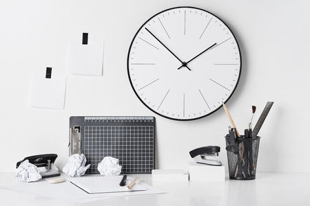 Office supplies, sticky notes and wall clock on white background, front view. Home workplace