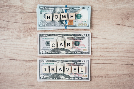Planning budget and wealth concept.  Words car, home and travel on dollar bills, top view Imagens