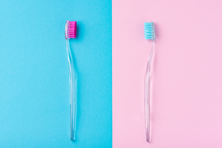 Two plastic toothbrushes on pastel blue and pink  background, flat lay style