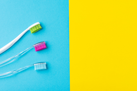 Three plastic toothbrushes on colorful blue and yellow  background, close up