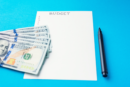 Planning budget concept. Notepad with word budget and dollar bills on blue background