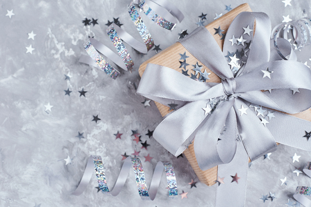 Gift box wrapped in kraft paper with gray bow and confetti in shape star, close up