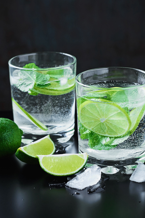 Two glasses of coctail with lime and mint on dark background
