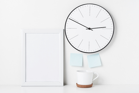 Mock up empty frame, round wall clock, two stickers and cup on white background. Home office minimal workspace desk
