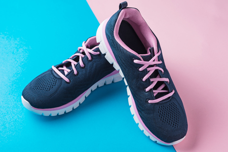 Pair of female sport shoes on pink and blue background Imagens