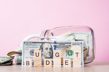 Saving money and planning budget concept. Dollar bills in glass saving bank and word budget on pink background