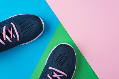 Female sport shoes for fitness on colorful background. Top view, flat lay