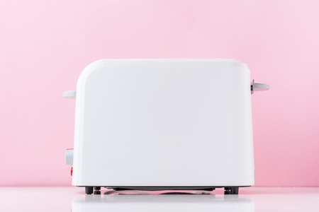 White toaster on pink background, close up
