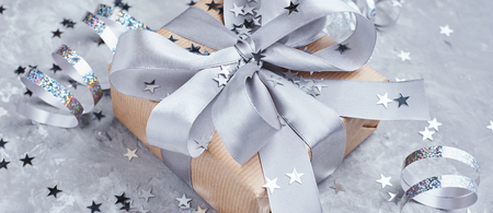 Gift box wrapped in kraft paper with gray bow and confetti, web banner