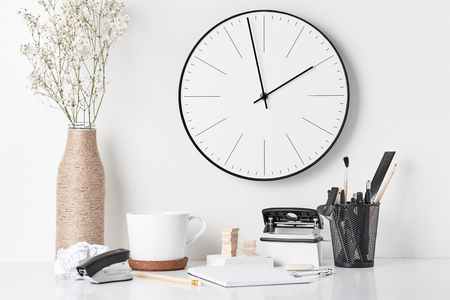 Office supplies, sticky notes and wall clock on white background, front view. Home   office workplace Imagens