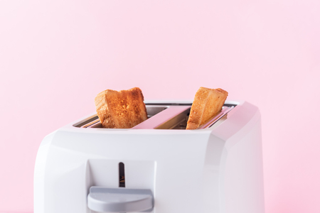 White toaster with  roasted toast bread on pink background, close up
