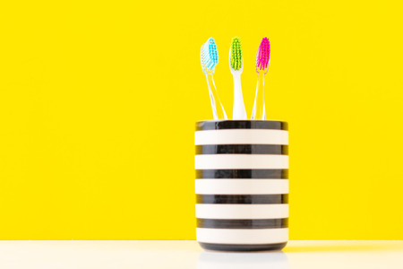 Three plastic colorful toothbrushes in glass on yellow background, close up Imagens