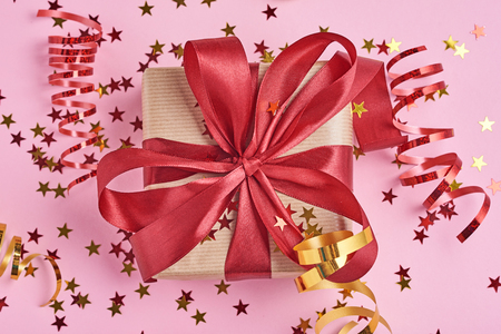 Gift box wrapped in kraft paper with red bow and confetti in shape star on pink background, close up