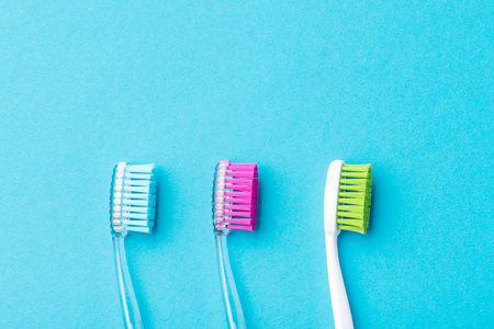 Three plastic colorful toothbrushes on blue background, close up