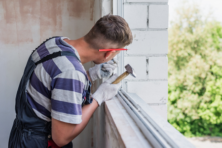 Process male worker repairing window in house, close up Imagens