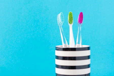 Three plastic colorful toothbrushes in glass on blue background, close up Imagens