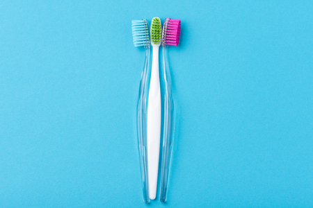 Two plastic colorful toothbrushes on blue background, close up Imagens