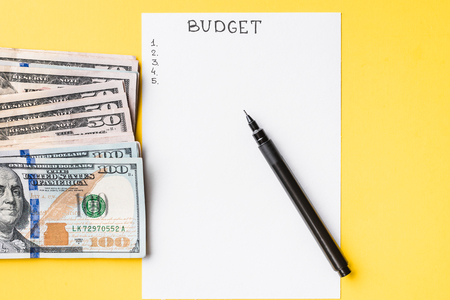 Planning budget concept. Notepad with word budget and dollar bills on yellow Imagens