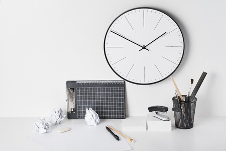 Office supplies and wall clock on white background, front view. Home workplace