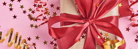 Gift box wrapped in kraft paper with red bow and confetti in shape star on pink background, web banner