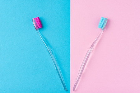 Two plastic toothbrushes on colorful blue and pink  background, close up