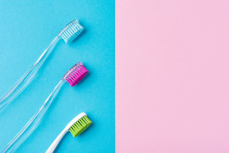 Three plastic toothbrushes on colorful blue and pink  background, close up