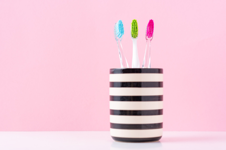Three plastic colorful toothbrushes in glass on pink background, close up