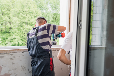 Process of man using screwdriver. The worker makes the installation of window