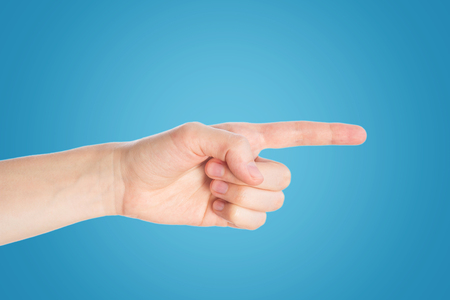 Pointing finger on blue background. Hand show direction gesture, close up Imagens