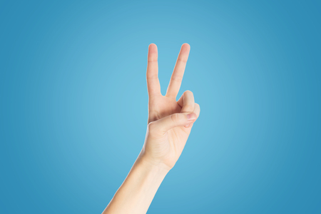 Positive gesture on blue background. Hand show viktory sign, close up Imagens