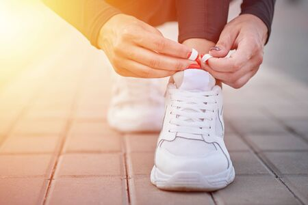 Woman get ready for run. Female hands tying shoelaces on sport sneakers Stockfoto