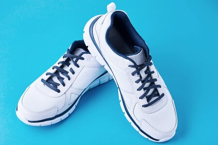 Pair of male white sneakers on blue background. Sport shoe close up