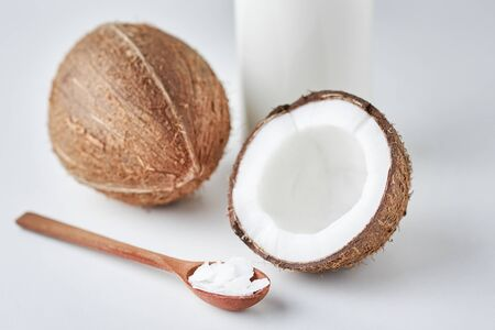 Coconut milk in glass bottle and fresh coconuts with half on gray background