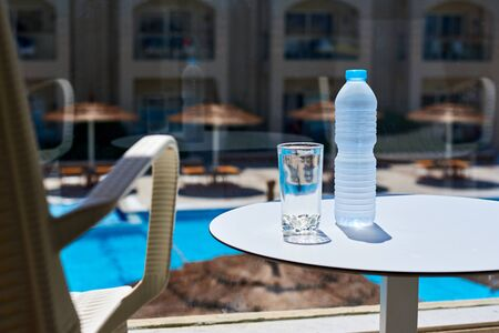 Bottle of water and glass on table at terrace in hotel against waterpool Banco de Imagens - 128518376