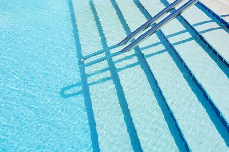 Background of water in blue swimming pool, water surface with sun reflection