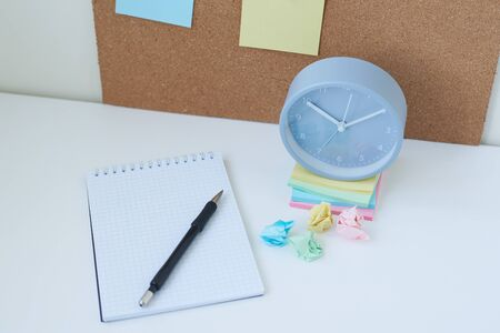 Alarm clock, and cork board with sticky notes. Home workplace concept