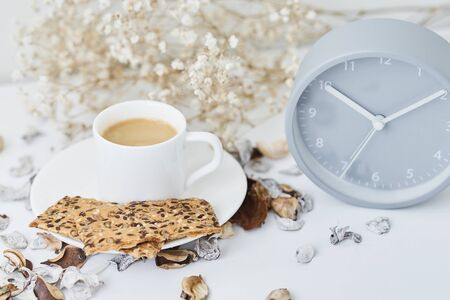 Cup of coffee and classic alarm clock on white table. Autumn or winter cozy background. Hygge style